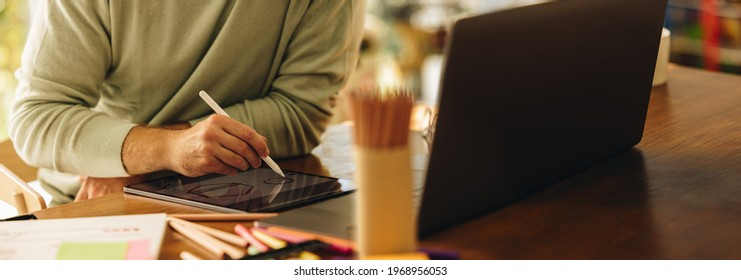 Cropped shot of a man drawing illustration on his graphic tablet. Artist using digital tablet to draw illustrations at home.