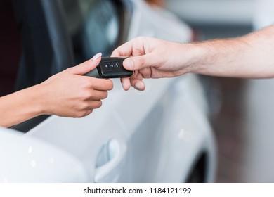 cropped shot of man giving car key to woman at dealership salon
