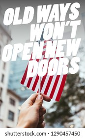 """cropped shot of man holding american flag in hand with blurred new york city street on background and """"old ways wont open new doors"""" quote"""
