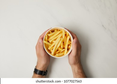 cropped shot of man holding bowl of french fries on white