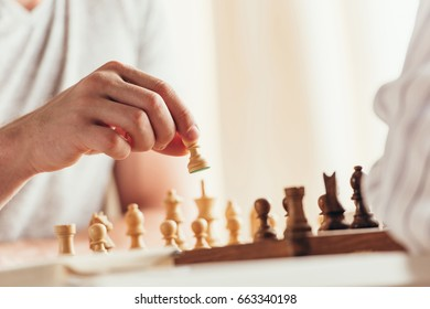 cropped shot of man moving chess figure during game