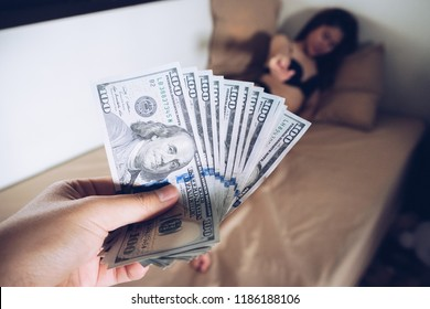 Cropped shot of man paying America dollars money to prostitute for sex. Prostitution concept.