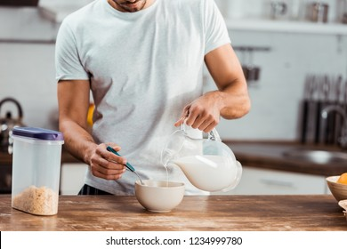 cropped shot of man pouring milk into bowl with corn flakes for breakfast