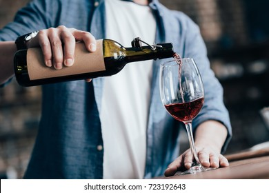cropped shot of man pouring red wine into glass