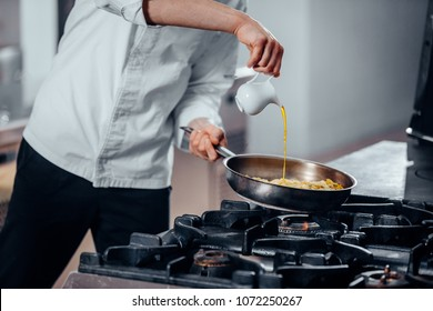 Cropped shot of a man pouring a sauce on the pot