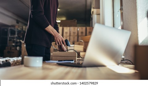 Cropped shot of man scanning the barcode of the shipment at his desk. Man working in a drop shipping office, preparing a parcel to deliver to the customer.