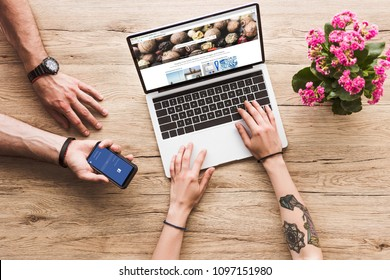 cropped shot of man with smartphone with facebook logo in hand and woman at tabletop with laptop with depositphotos website and kalanchoe flower