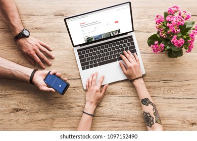 cropped shot of man with smartphone with facebook logo in hand and woman at tabletop with laptop with airbnb website and kalanchoe flower