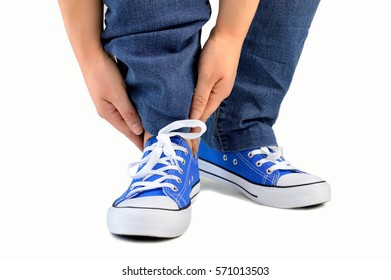cropped shot of a man with sneakers and touching his ankles isolated on white background