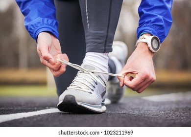Cropped shot of a man tying his shoelaces before running.