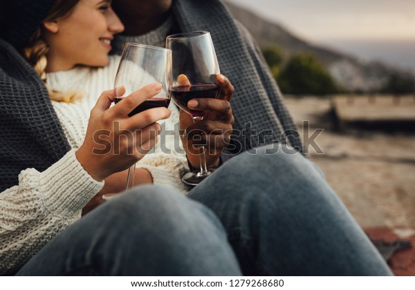 Cropped shot of a man and woman wrapped in blanket sitting together toasting wine while on a picnic. Couple enjoying a picnic outdoors with wine on a cold winter day.