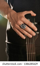 Cropped shot of man's hand, touching headstock of guitar. The guy is wearing signet-ring in the view of a skull. The man is wearing black clothes, posing against the dark background with highlight.