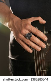 Cropped shot of man's hand, touching headstock of guitar. The guy is wearing signet-ring in view of Gorgon's head. The man is wearing black clothes, posing against the dark background with highlight.
