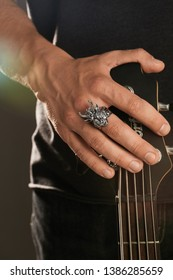 Cropped shot of man's hand, touching the headstock of guitar. The guy is wearing a massive signet-ring in view of demon Baphomet. The man is wearing black clothes, posing against the dark background.