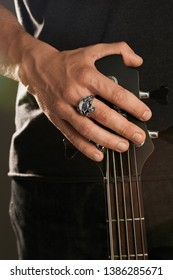 Cropped shot of man's hand, touching headstock of guitar. The guy is wearing signet-ring in the view of skull enclosed in claws. The man is wearing black clothes, posing against the dark background.