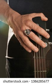 Cropped shot of man's hand, touching the headstock of guitar. The guy is wearing signet-ring in the view of Grim Reaper in hood. The man is wearing black clothes, posing against the dark background.
