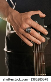 Cropped shot of man's hand, touching headstock of guitar. The guy is wearing signet-ring in the view of skull with opened jaws. The man is wearing black clothes, posing against the dark background.