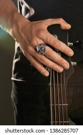 Cropped shot of man's hand, touching headstock of guitar. The guy is wearing signet-ring in the view of skull with asymmetric face. The man is wearing black clothes, posing on the dark background.