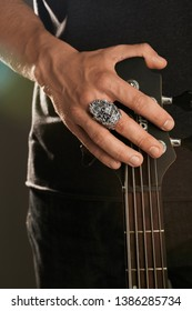 Cropped shot of man's hand, touching headstock of guitar. The guy is wearing a massive signet-ring in the view of ork's head. The man is wearing black clothes, posing against the dark background.