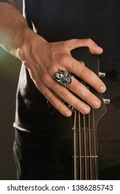 Cropped shot of man's hand, touching headstock of guitar. The guy is wearing massive signet-ring in the view of demon's head. The man is wearing black clothes, posing against the dark background.