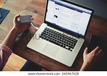 Cropped shot of a man's hands using a laptop at home while holding credit card, data security, on-line shopping at home, cross process, filtered image, focused on the left hand with gift card