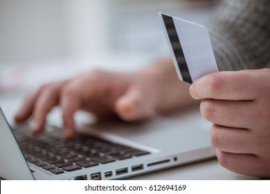 Cropped shot of a man's hands working on a laptop and holding credit card