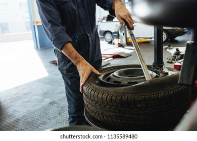 Cropped shot of mechanic removing the tire from rim on machine. Hands of technician taking out the automobile wheel from rim.