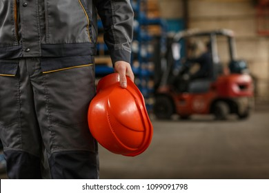 Cropped shot of a mid section of a male industrial worker wearing uniform holding protective hardhat, standing at the storage of metalworking company. Heavy industry concept