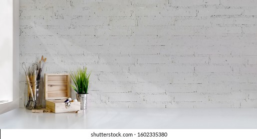 Cropped shot of minimal artist workplace with painting tools on white table and white brick wall background