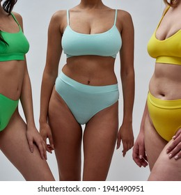 Cropped shot of mixed race young woman posing together with her female friends in colorful underwear isolated over light background. Body positivity concept