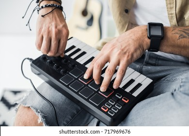 cropped shot of modern dj working with MPC pad