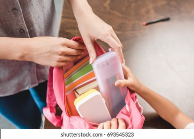 cropped shot of mother and daughter preparing backpack with school supplies