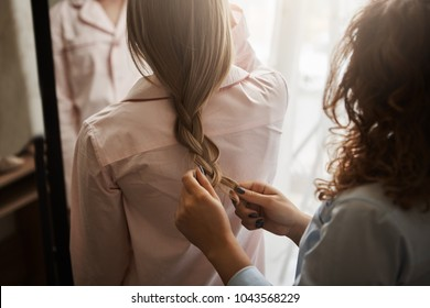 Cropped shot of mother and daughter standing in nightwear while mom making braid for her cutie, combing hair and looking in mirror to see result, getting dressed in morning