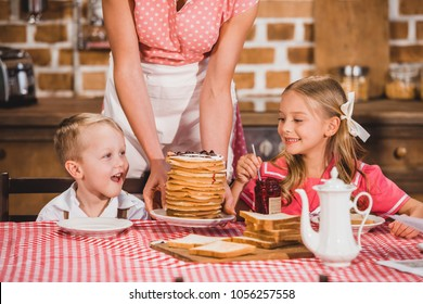 cropped shot of mother putting pancakes on table and looking at cute smiling kids having breakfast, 50s style family