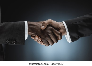 cropped shot of multicultural businessmen handshake isolated on black