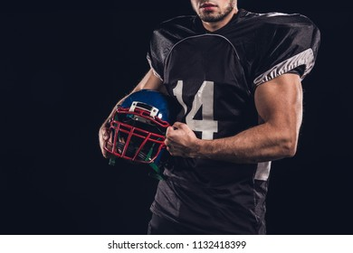 cropped shot of muscular american football player holding helmet isolated on black