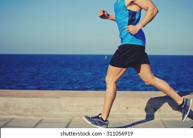 Cropped shot with muscular build man running along the seashore with copy space area for your text message or advertising content, male jogger working out outdoors o the beach at sunny afternoon