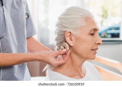 cropped shot of nurse wearing hearing aid to senior patient