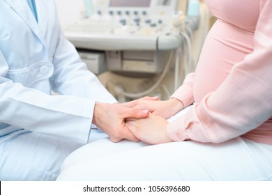 cropped shot of obstetrician gynecologist holding hands of pregnant woman