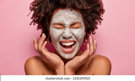 Cropped shot of overjoyed dark skinned woman has broad smile, keeps hands near face, applies clay mask, Afro hairstyle, enjoys softness of skin, isolated over pink background. Facial treatments