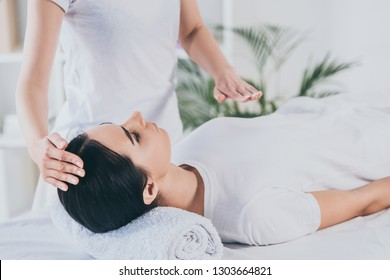 cropped shot of peaceful young woman receiving reiki healing treatment on head and chest