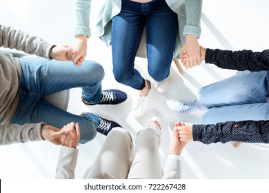 cropped shot of people holding hands during group therapy