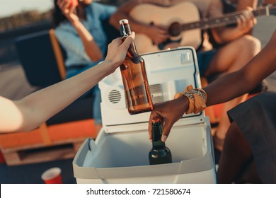 cropped shot of people taking beer out of portable fridge
