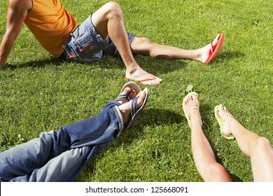 cropped shot of people's legs while sitting on the grass