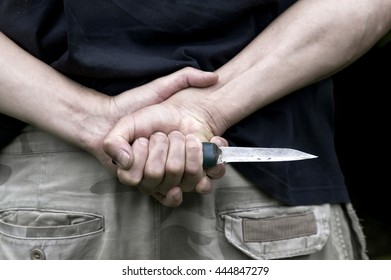 Cropped shot of a person hiding a hand made knife behind his back, concept of conflict and aggression