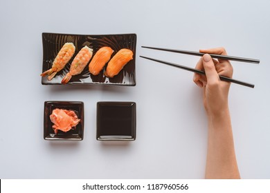 cropped shot of person holding chopsticks and eating delicious sushi isolated on white