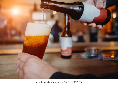 Cropped shot of person holding glass and pouring beer from bottle - Shutterstock ID 1445521109