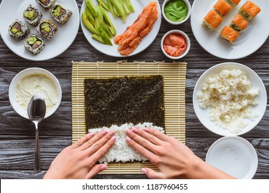 cropped shot of person preparing sushi with rice and nori, gourmet ingredients on table