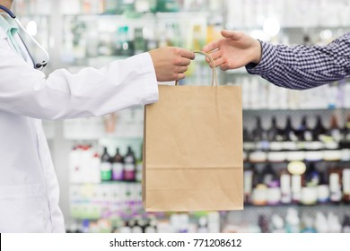 Cropped shot of a pharmacist in white labcoat handing shopping bag with purchased medications to his male client pharmacy drugstore health buying consumer customer purchasing retail store.