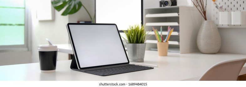 Cropped shot of portable office desk with mock-up computer devices, supplies and decorations on white table  - Shutterstock ID 1689484015